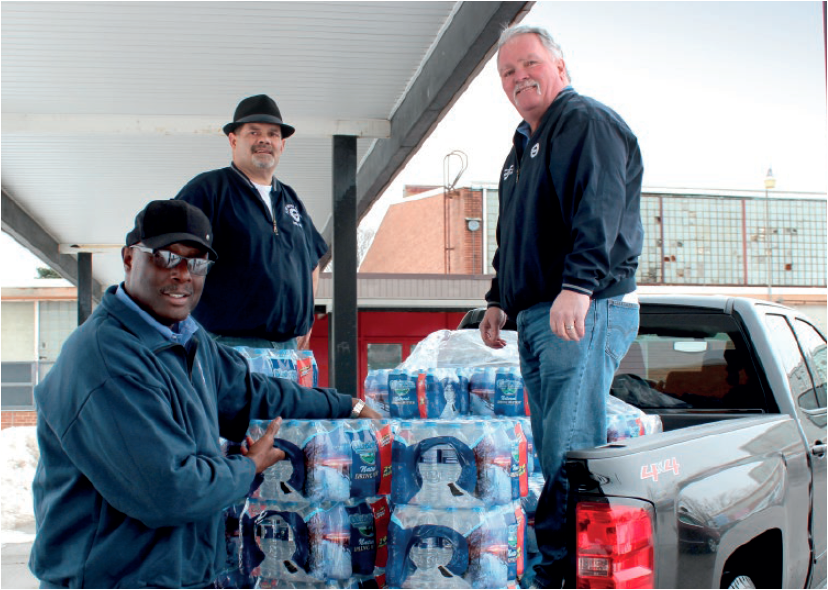 UAW Region 1D Director Gerald Kariem, left, Local 659 Recording Secretary Tim Duplanty, and Region 1D Assistant Director Steve Dawes at the Brennan Community Center get set to distribute water donated by UAW members.