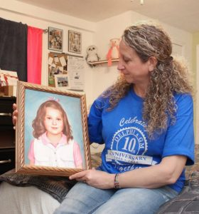 Tina Kollek sits in Cynthia's room with a painting of her daughter.