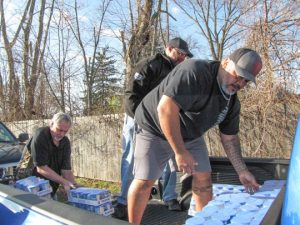 UAW Local 12's Chris Huddleston, left, Committeeman Brian Sims, and Mario Duran load up food to be donated to the hungry in Toledo.